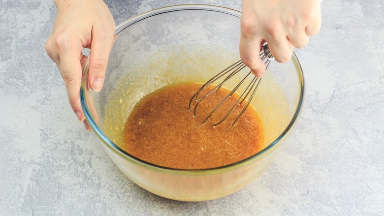 Whisking together eggs and brown sugar in a bowl