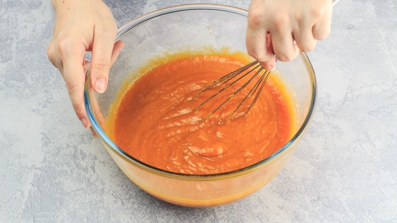 Whisking together wet ingredients in a bowl for Pumpkin Chocolate Chip Bread