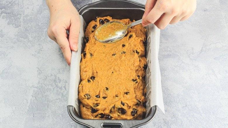 Spreading Pumpkin Chocolate Chip Bread batter into loaf pan