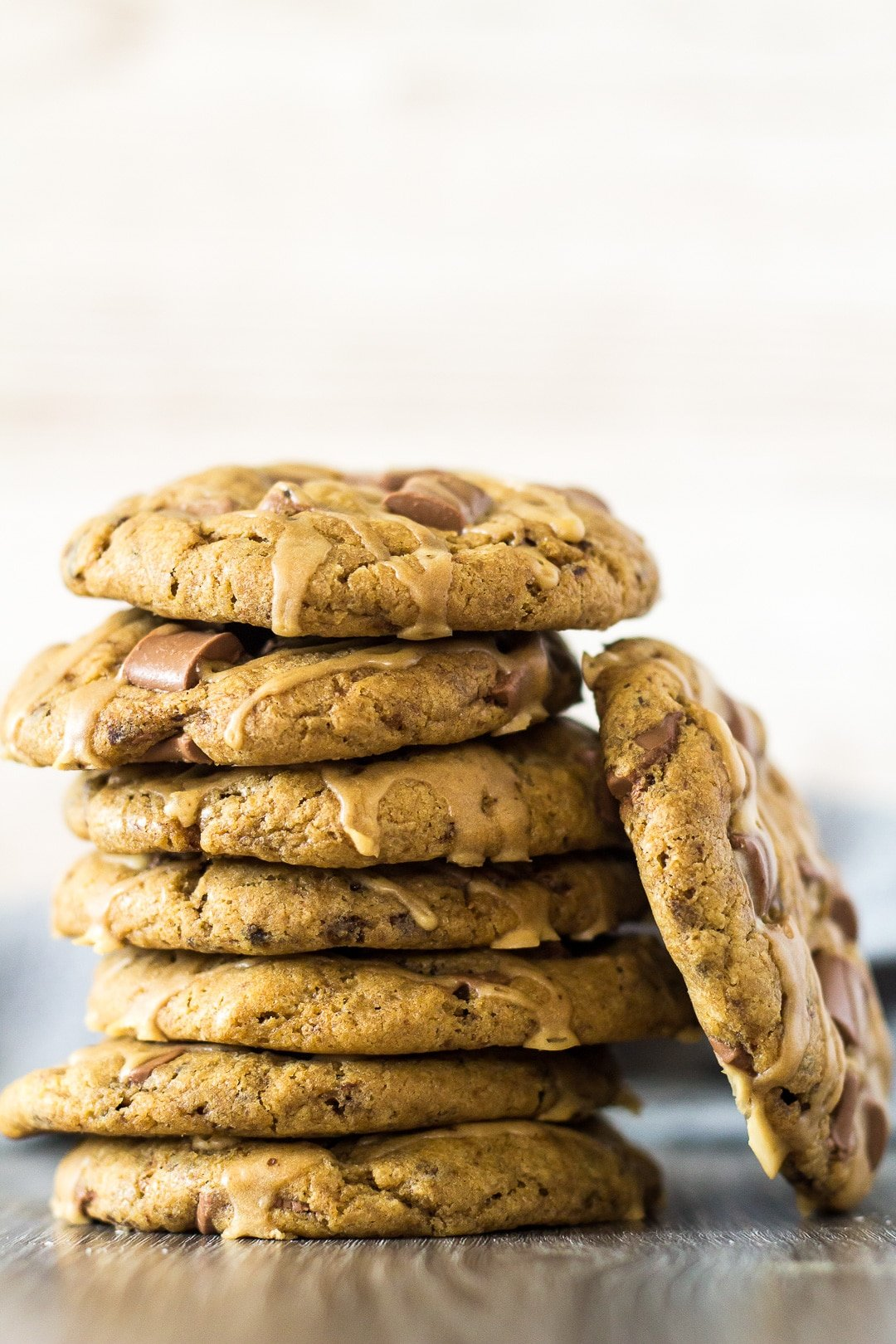 A stack of Chocolate Chip Coffee Cookies with one cookie leaning up against the stack.