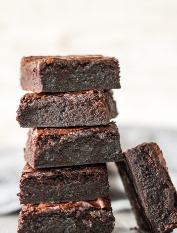 A sideview of a tall stack of Fudgy Brownies.
