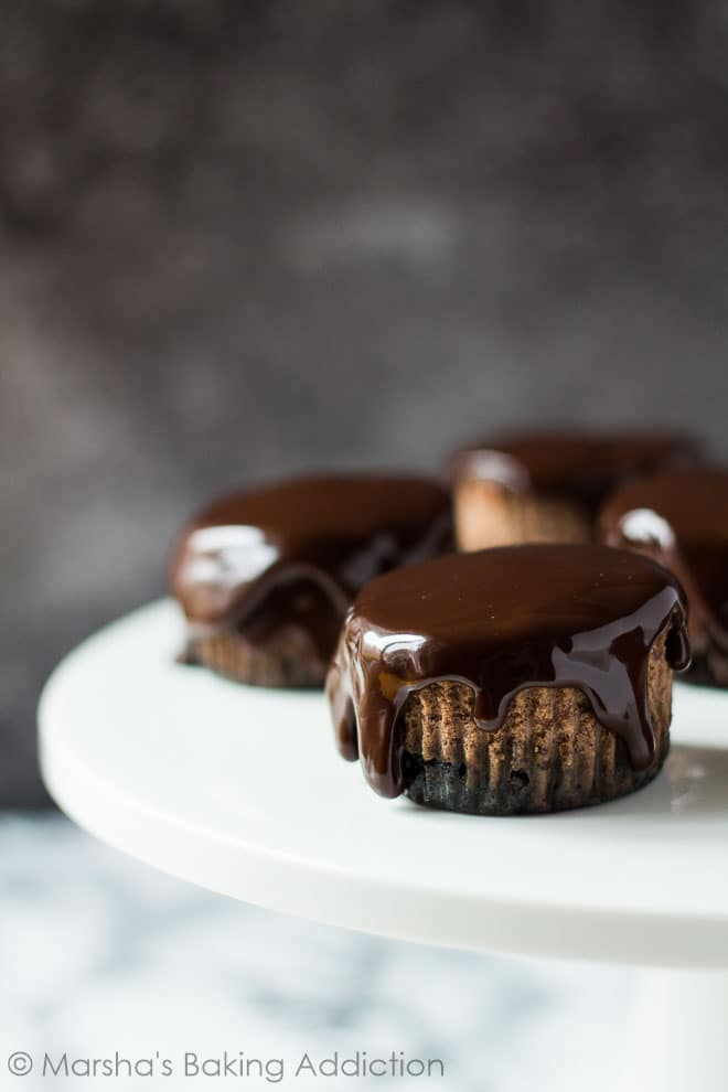 Close-up of Mini Chocolate Orange Cheesecakes dripping with thick chocolate ganache assembled on white cake stand.