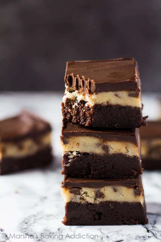 A stack of Chocolate Chip Cookie Dough Brownies on marble background.