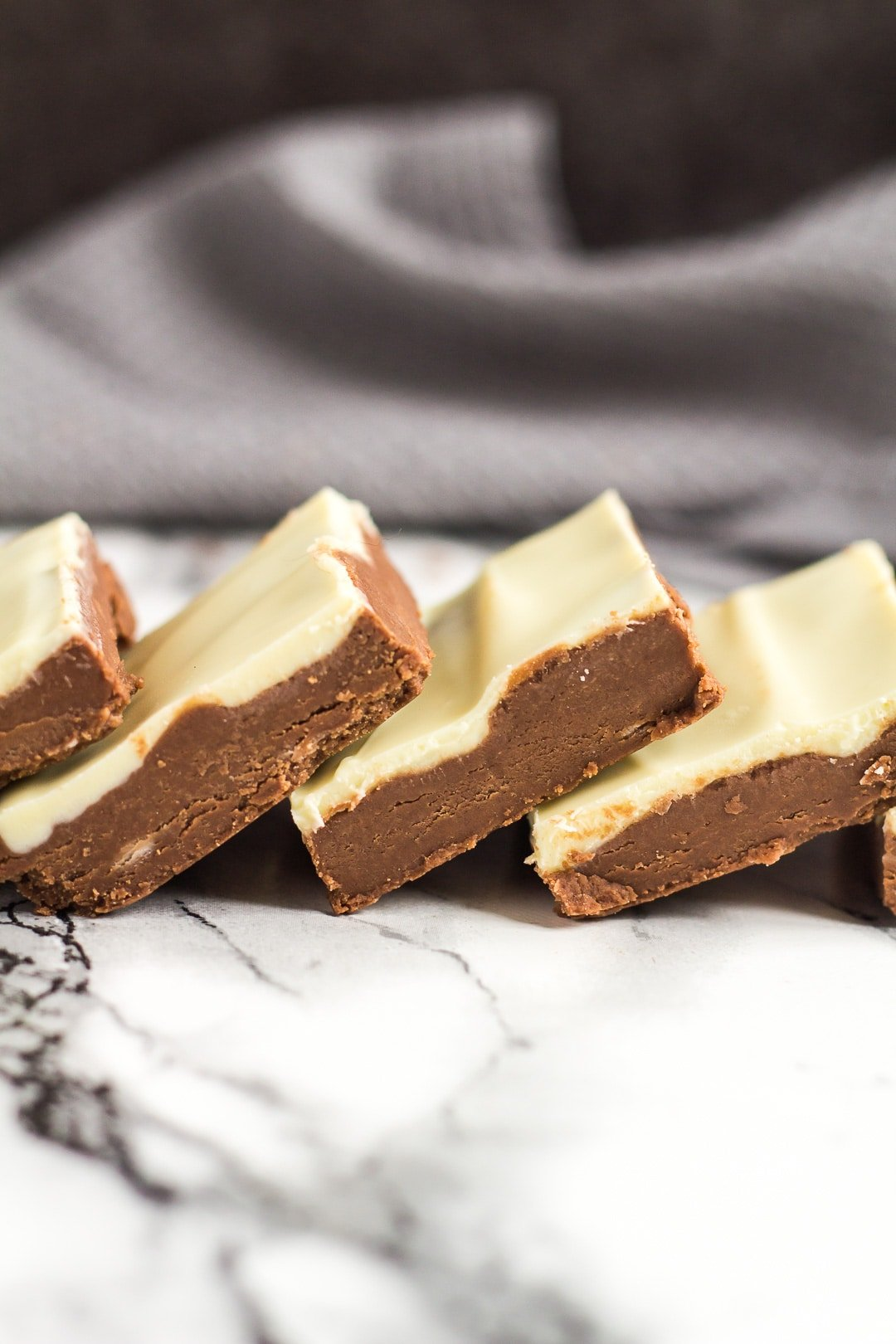 No-Bake White Chocolate Nutella Bars overlapped in a row on a marble background.