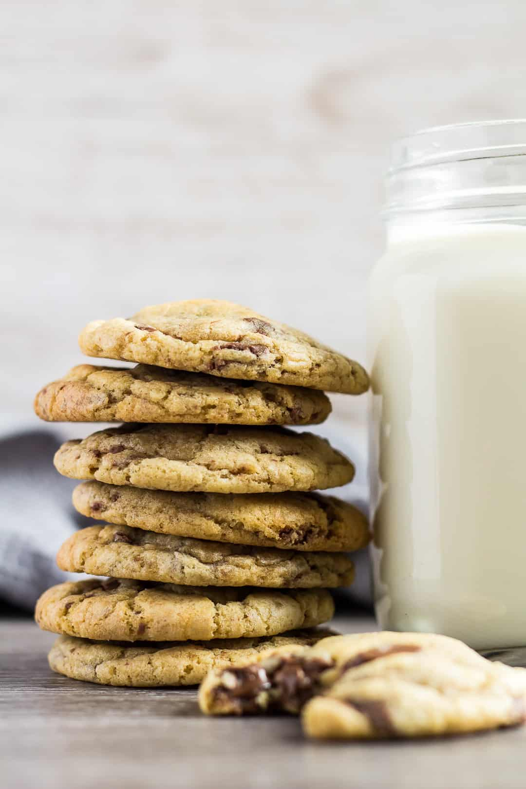 Tall stack of Chocolate Chip Cookies next to glass of milk.