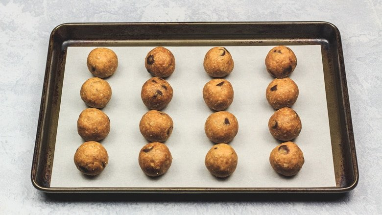 Peanut butter mixture rolled into balls on tray.