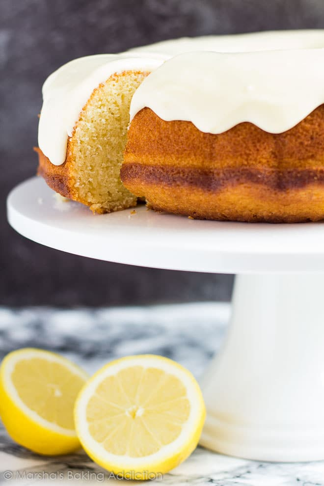 Lemon Bundt Cake topped with a thick icing with a slice cut out on a white cake stand.