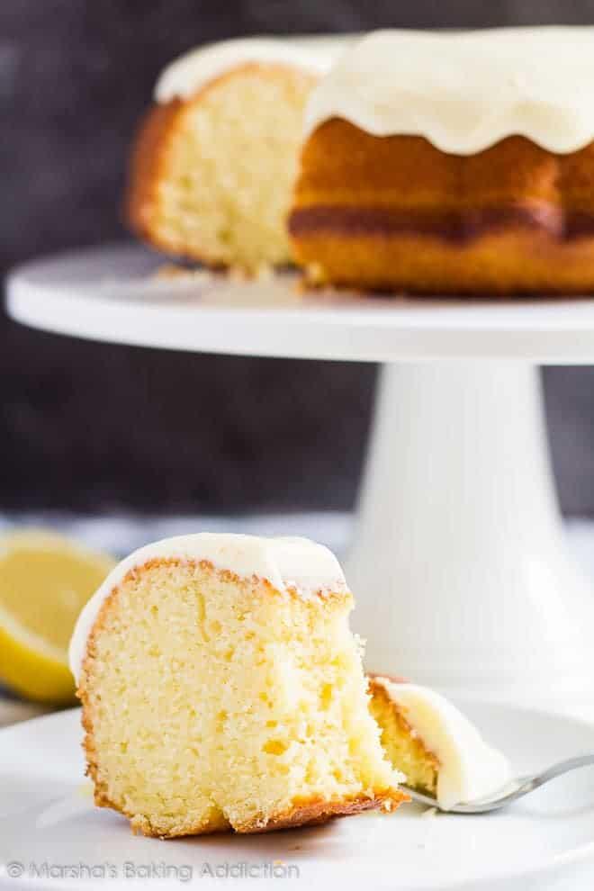 A slice of Lemon Bundt Cake served on a white plate with a fork.