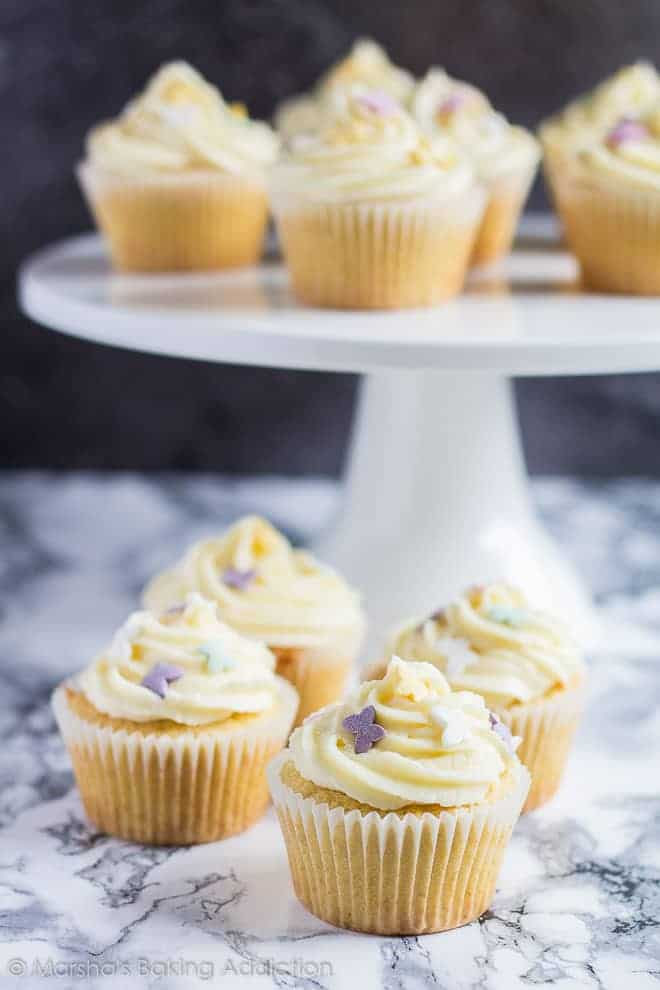 Perfect Vanilla Cupcakes served on a white cake stand and on marble background.