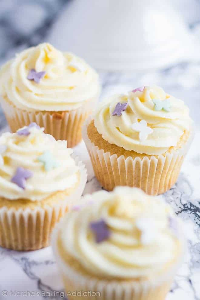 Perfect Vanilla Cupcakes topped with butterfly sprinkles on marble background.