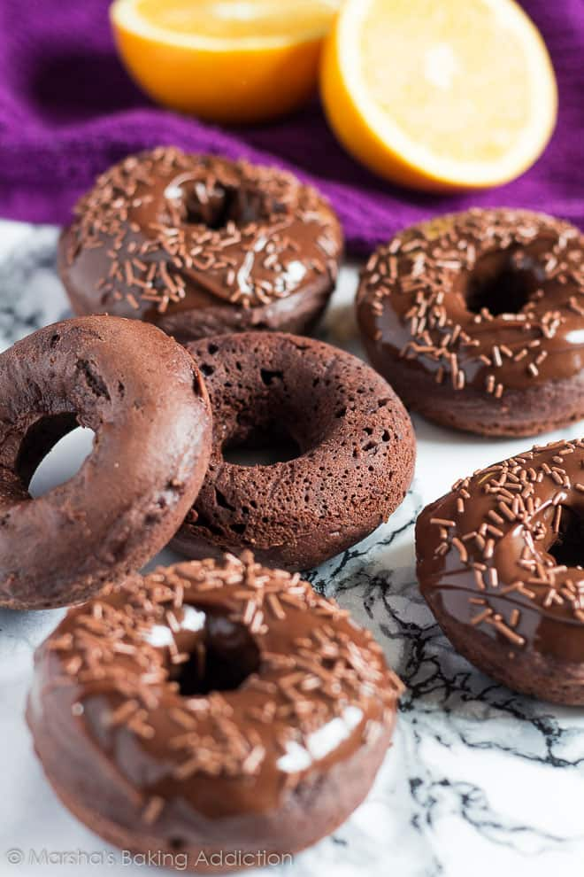 Baked Double Chocolate Orange Doughnuts scattered on a marble background.