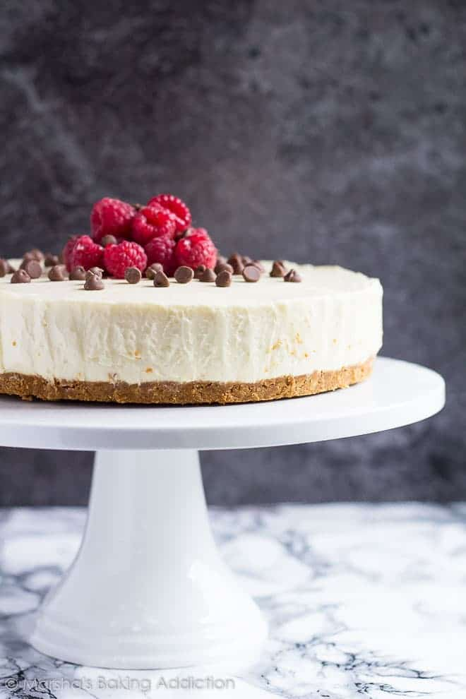 White Chocolate Tortetopped with chocolate chips and raspberries served on a white cake stand.