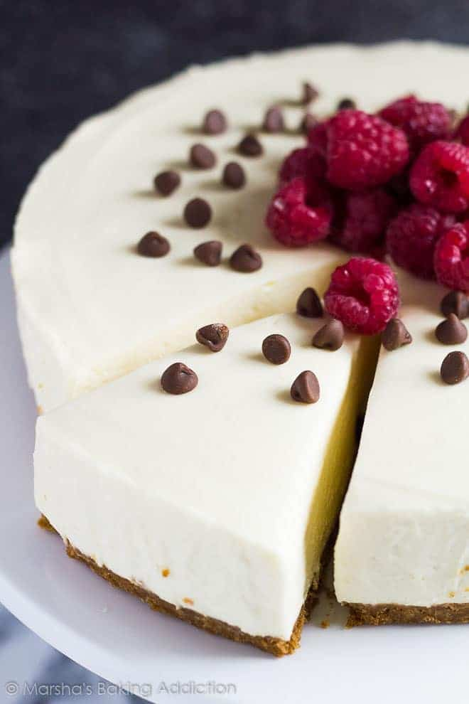 White Chocolate Torte topped with raspberries and chocolate chips with a slice cut out.