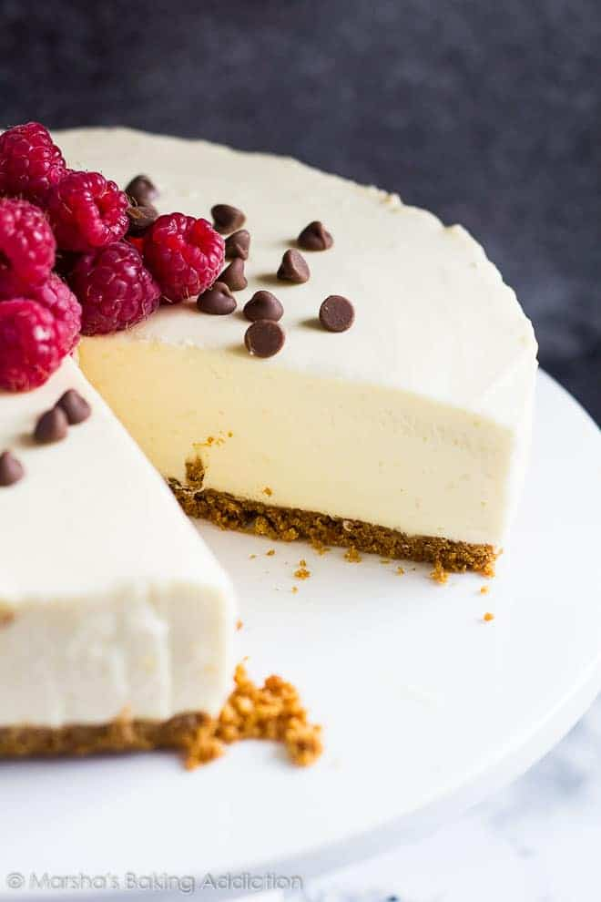 White Chocolate Tortetopped with raspberries and chocolate chips served on a white cake stand with a slice removed.