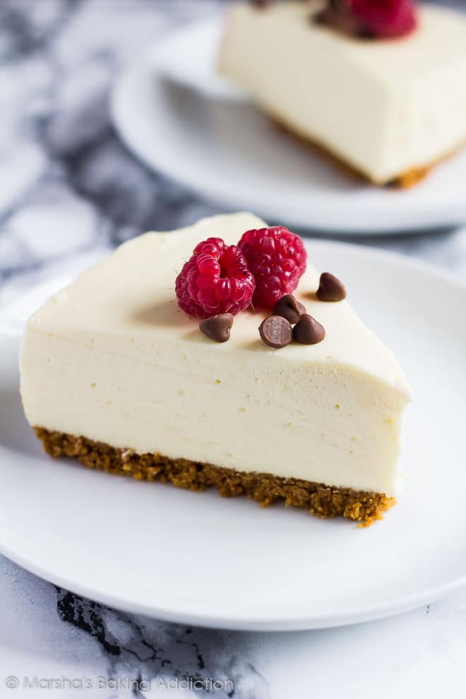 A slice of White Chocolate Torte served on a white plate with chocolate chips and raspberries.