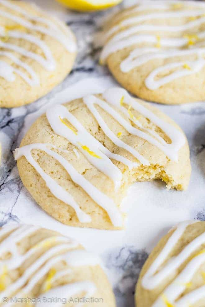 Soft and Chewy Lemon Cream Cheese Cookiesdrizzled with a glaze with a bite taken out of one cookie.