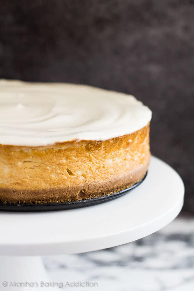 Perfect Vanilla Cheesecake topped with a sour cream topping served on a white cake stand.
