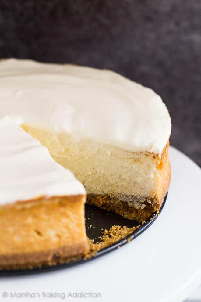 Perfect Vanilla Cheesecake served on a white cake stand with a slice removed.