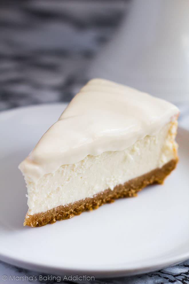 A slice of Perfect Vanilla Cheesecakewith a sour cream topping served on a white plate.