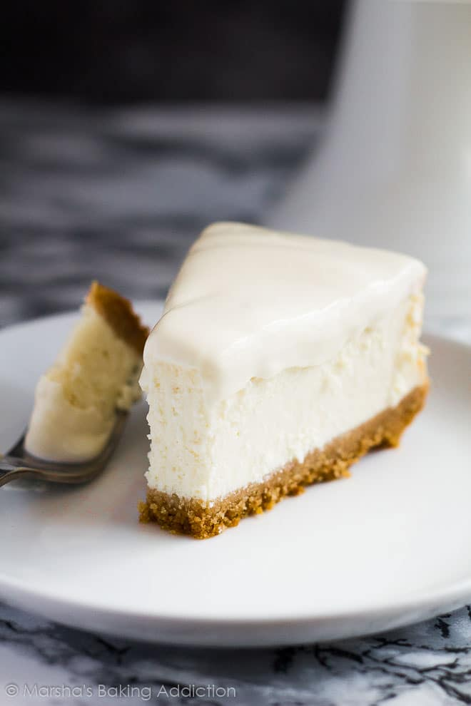 Perfect Vanilla Cheesecakeslice with a sour cream topping served on a white plate with a fork.