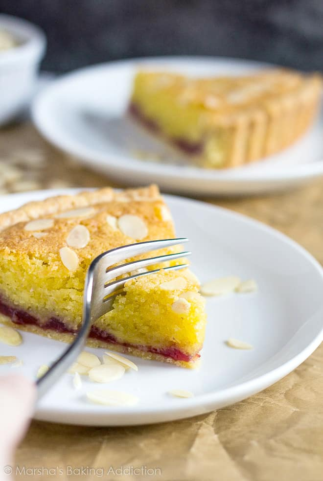 A slice of Bakewell Tart served on a white plate with a fork about to break a piece off.