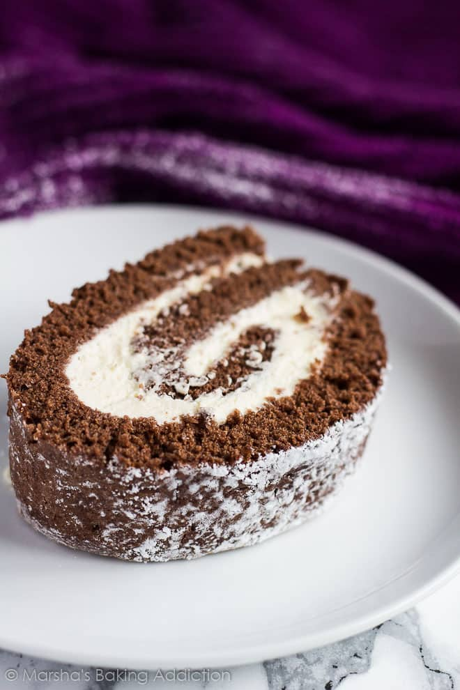 A thick slice of Chocolate Swiss Roll served on a white plate.