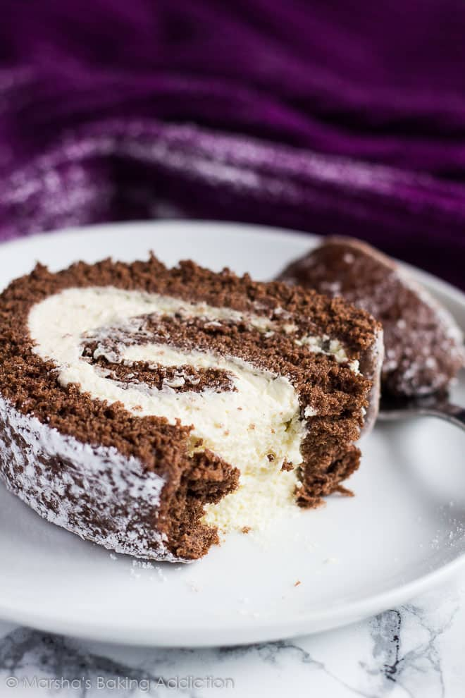 A slice of Chocolate Swiss Roll served on a white plate with a fork.