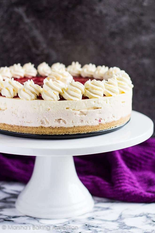 No-Bake White Chocolate Raspberry Cheesecaketopped with piped swirls on a white cake stand.