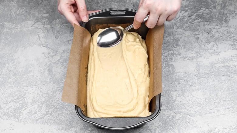Spreading cake batter into loaf pan.