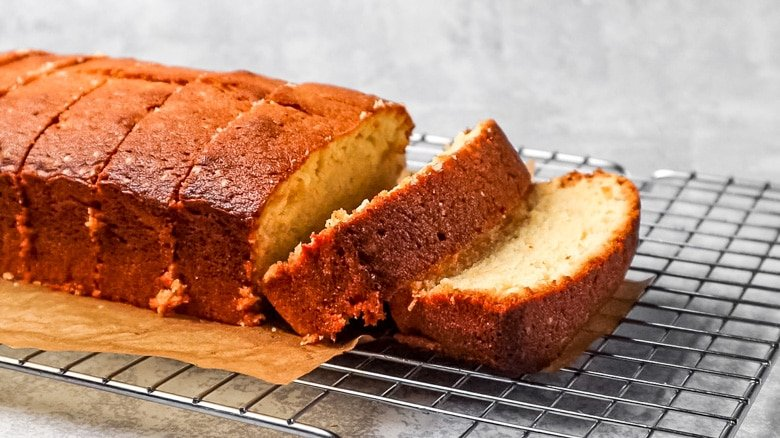 Pound cake cut into slices on wire rack.