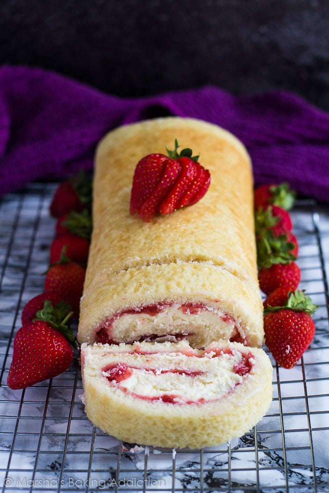 Strawberries and Cream Swiss Rollon a wire rack with whole strawberries.