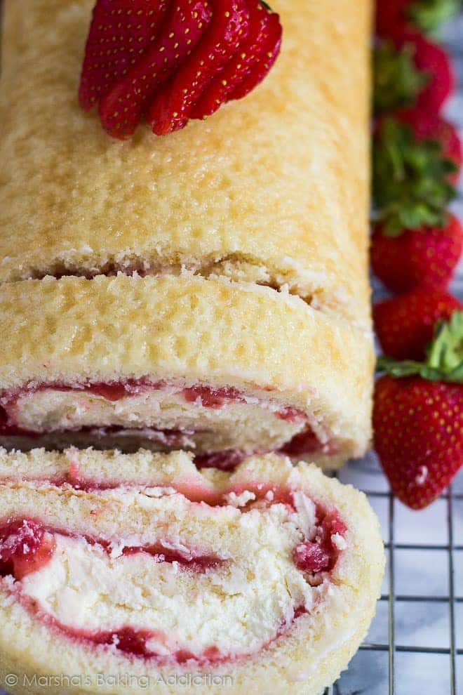 Overhead shot of Strawberries and Cream Swiss Rollon a wire rack with whole strawberries.