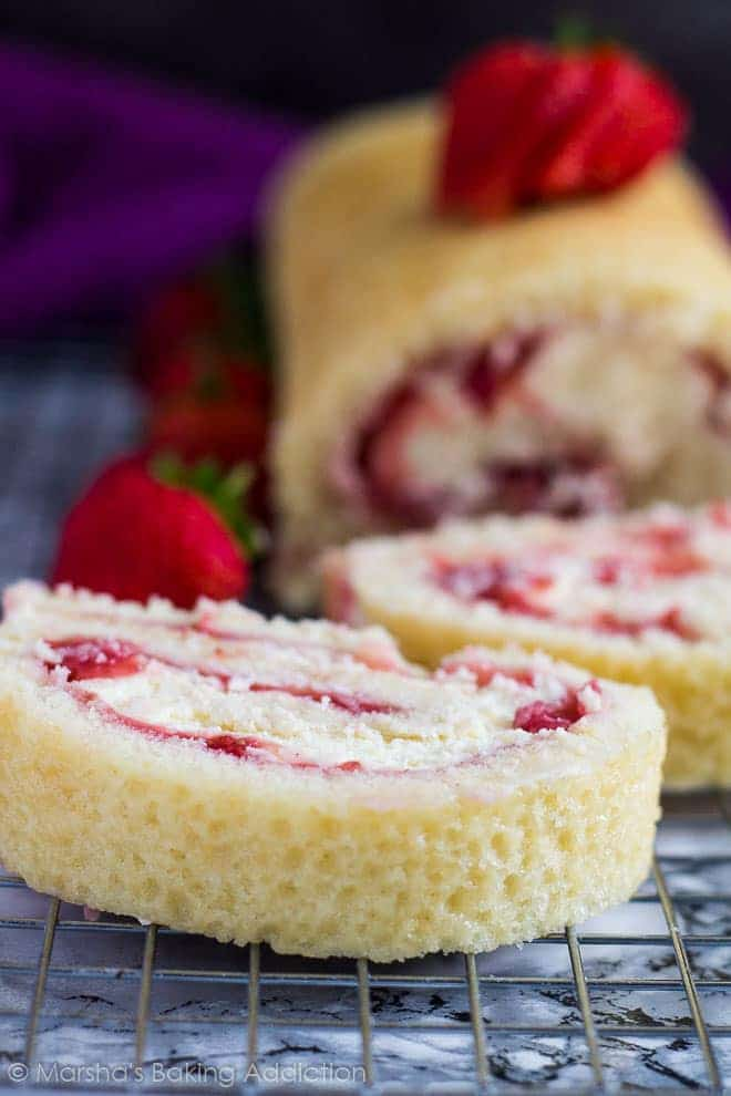 Strawberries and Cream Swiss Rollcut into slices on a wire rack.