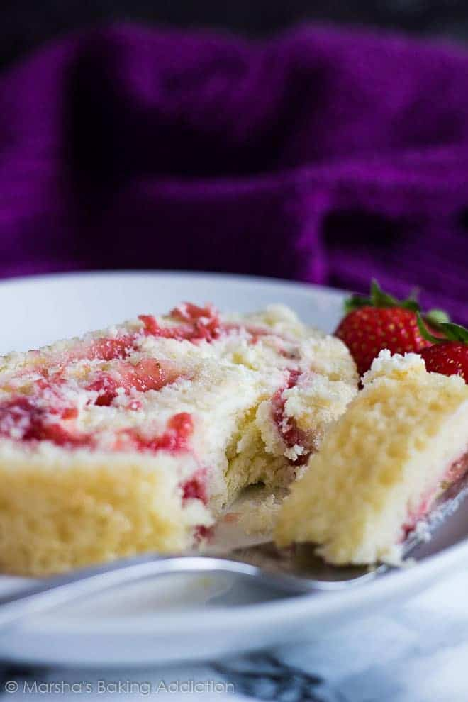A slice of Strawberries and Cream Swiss Roll served on a white plate with a fork.