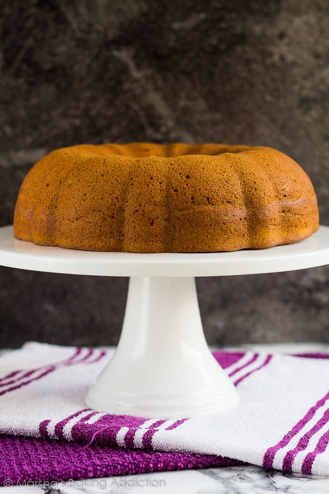 Cheesecake Swirl Pumpkin Bundt Cake with no frosting on a white cake stand.