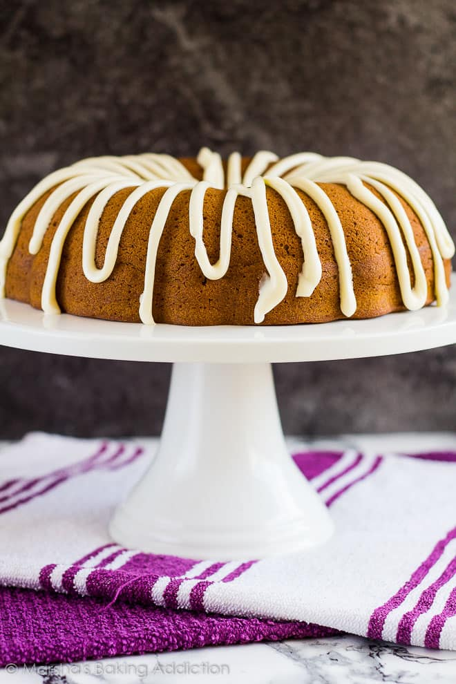 Cheesecake Swirl Pumpkin Bundt Cake topped with cream cheese frosting on a white cake stand.