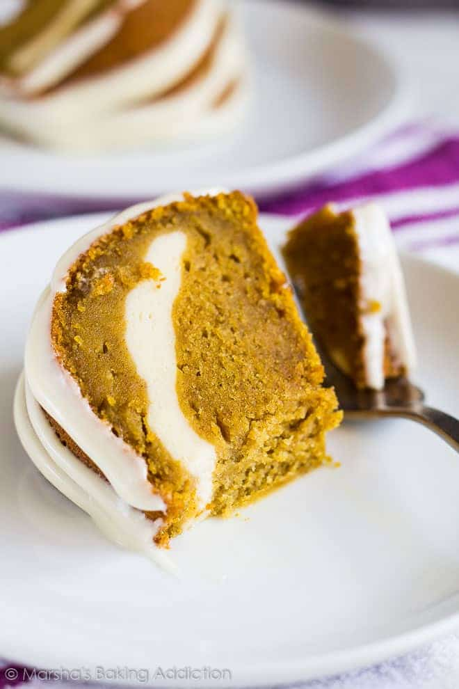 A slice of Cheesecake Swirl Pumpkin Bundt Cake served on a white plate with a fork.