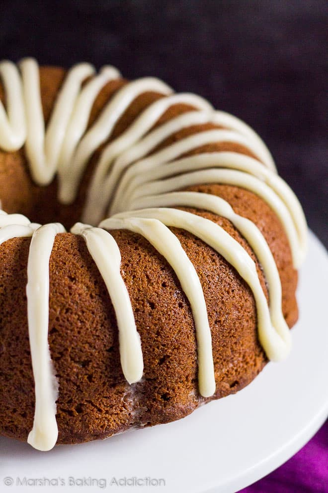 Cheesecake Swirl Carrot Bundt Cake drizzled with cream cheese frosting on a white cake stand.