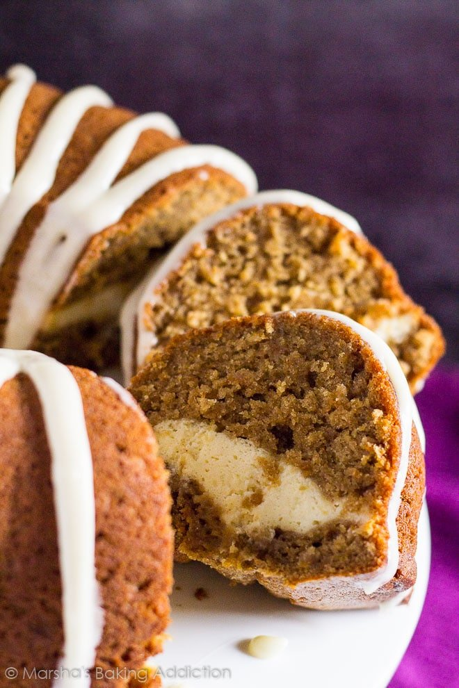 Cheesecake Swirl Carrot Bundt Cake with two slices cut out overlapped on a white cake stand.