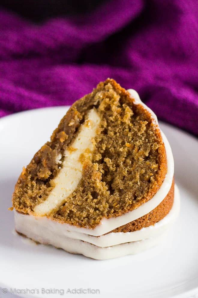 A thick slice of Cheesecake Swirl Carrot Bundt Cake served on a white plate.