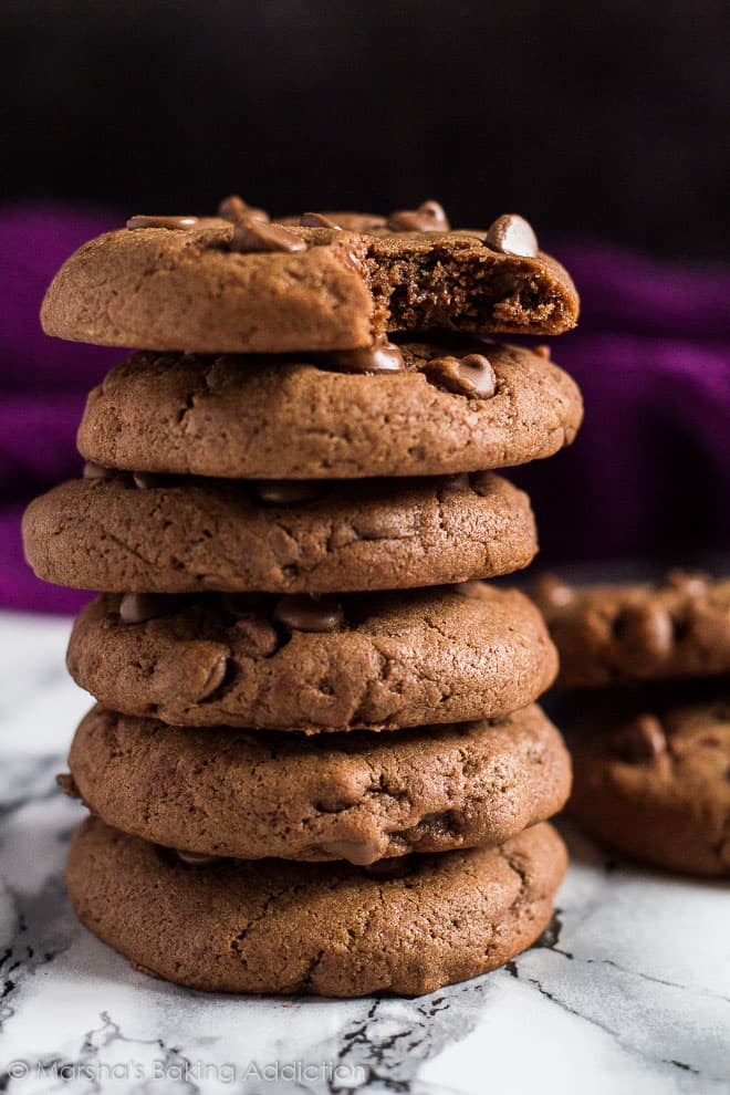 A tall stack of Double Chocolate Cream Cheese Cookieswith bite taken out of the top cookie.