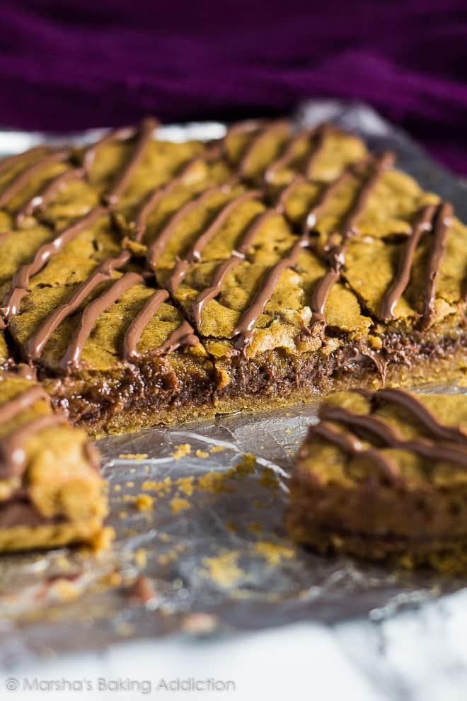 Nutella Stuffed Pumpkin Cookie Bars on foil with slices removed to show gooey Nutella centre.
