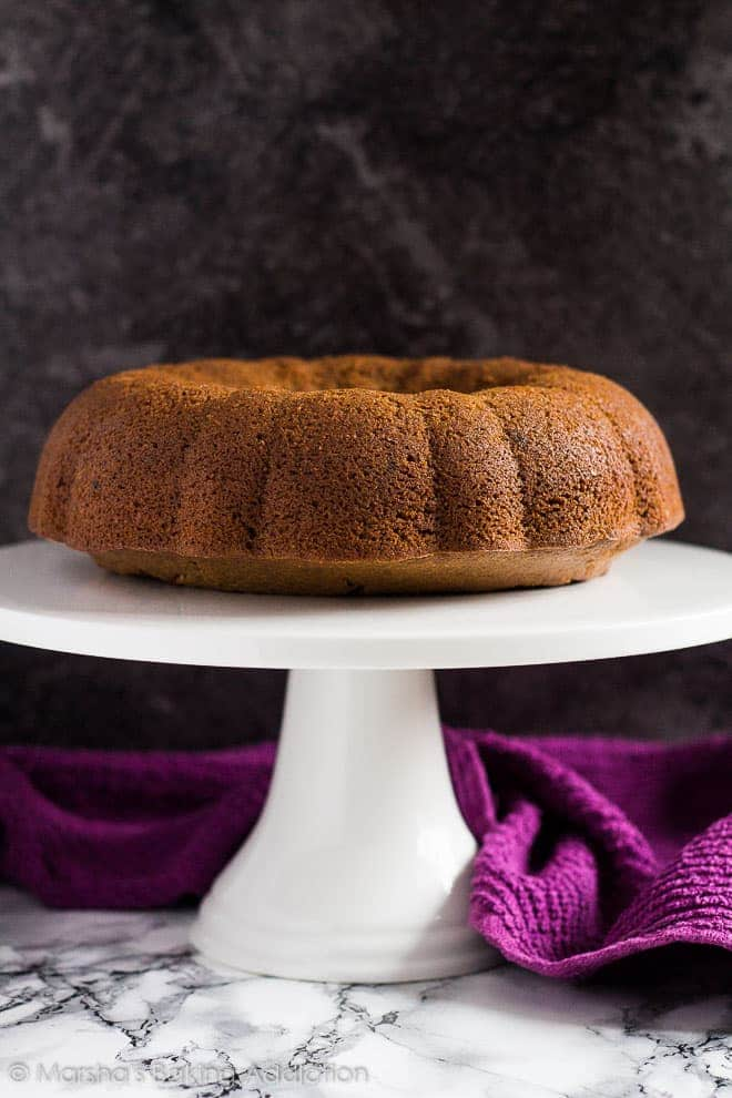 An unglazed Coffee Bundt Cake on a white cake stand.