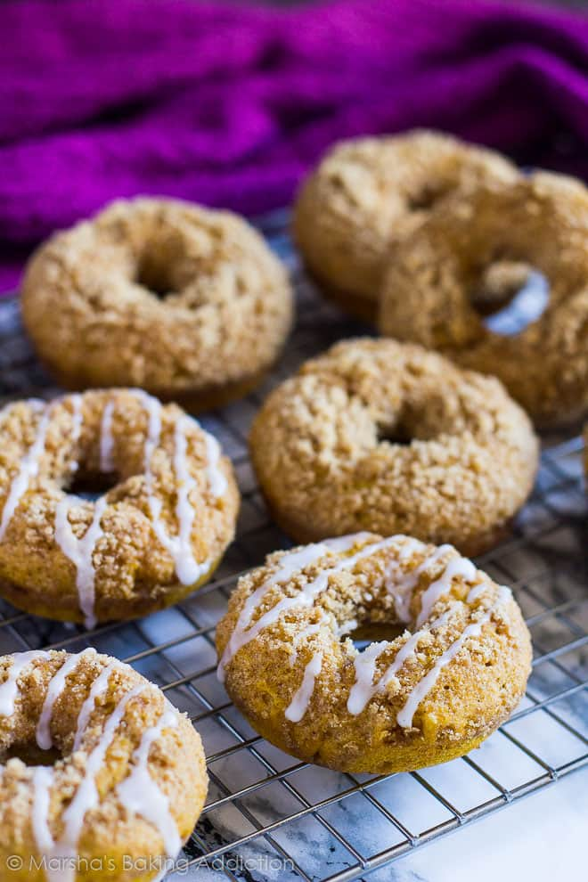 Baked Pumpkin Streusel Doughnuts drizzled with a glaze on a wire rack.
