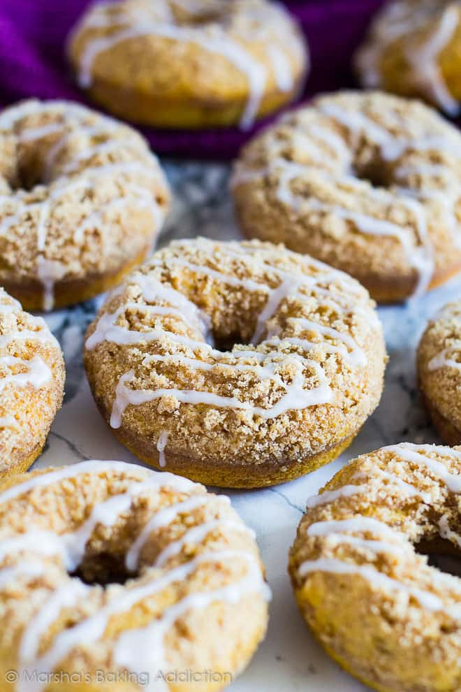 Baked Pumpkin Streusel Doughnuts drizzled with a glaze on a marble background.