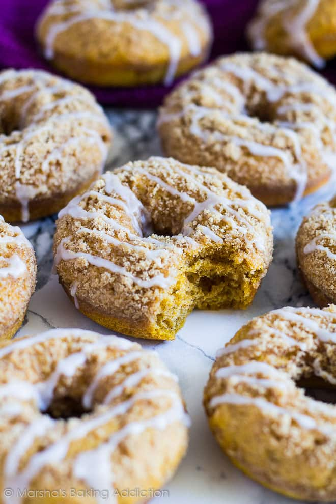 Baked Pumpkin Streusel Doughnuts with a bite taken out of one of them on marble background.
