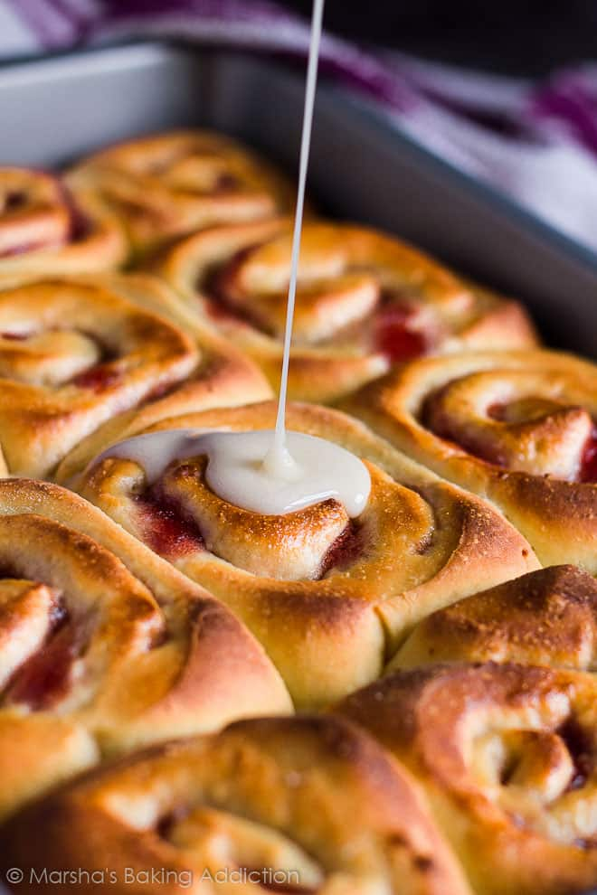 A sweet glaze being poured onto Bakewell Sweet Rolls in a rectangle baking pan.