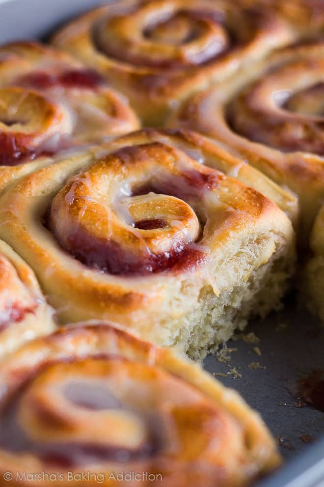 Bakewell Sweet Rolls drizzled in a sweet glaze with a sweet roll removed in a rectangle baking pan.