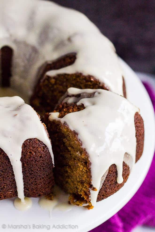 A glazed Gingerbread Bundt Cake with a thick slice cut out on a white cake stand.