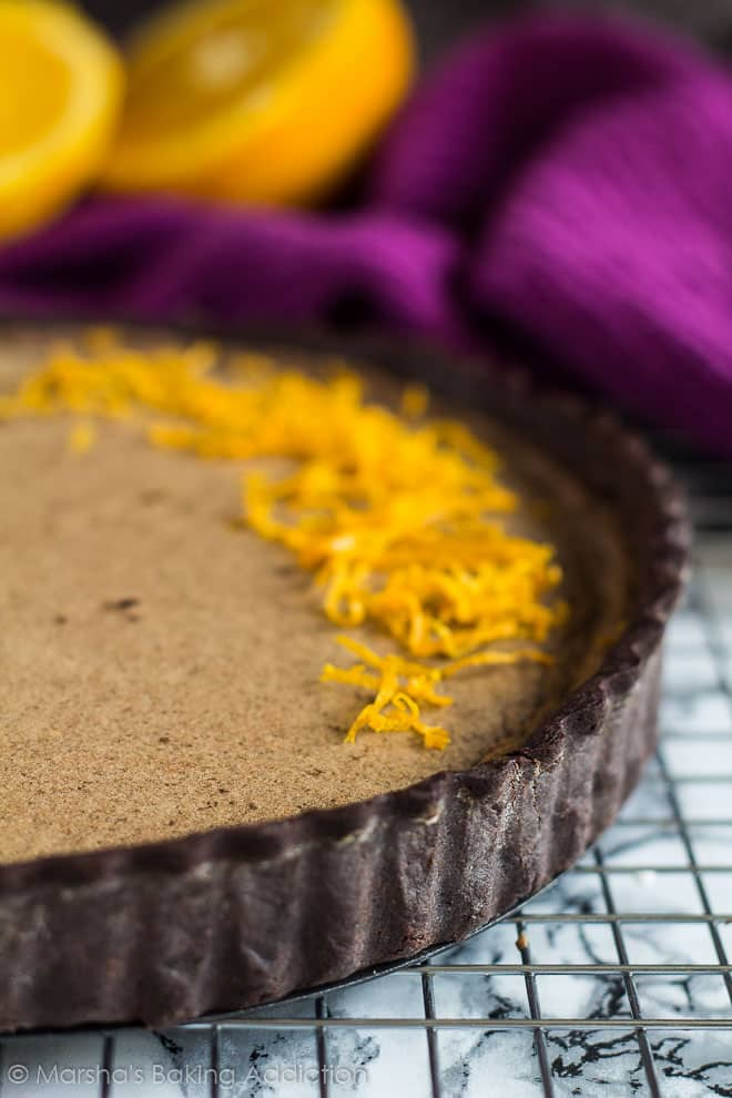 Close-up of the chocolate crust on Dark Chocolate Orange Tart on a wire rack.